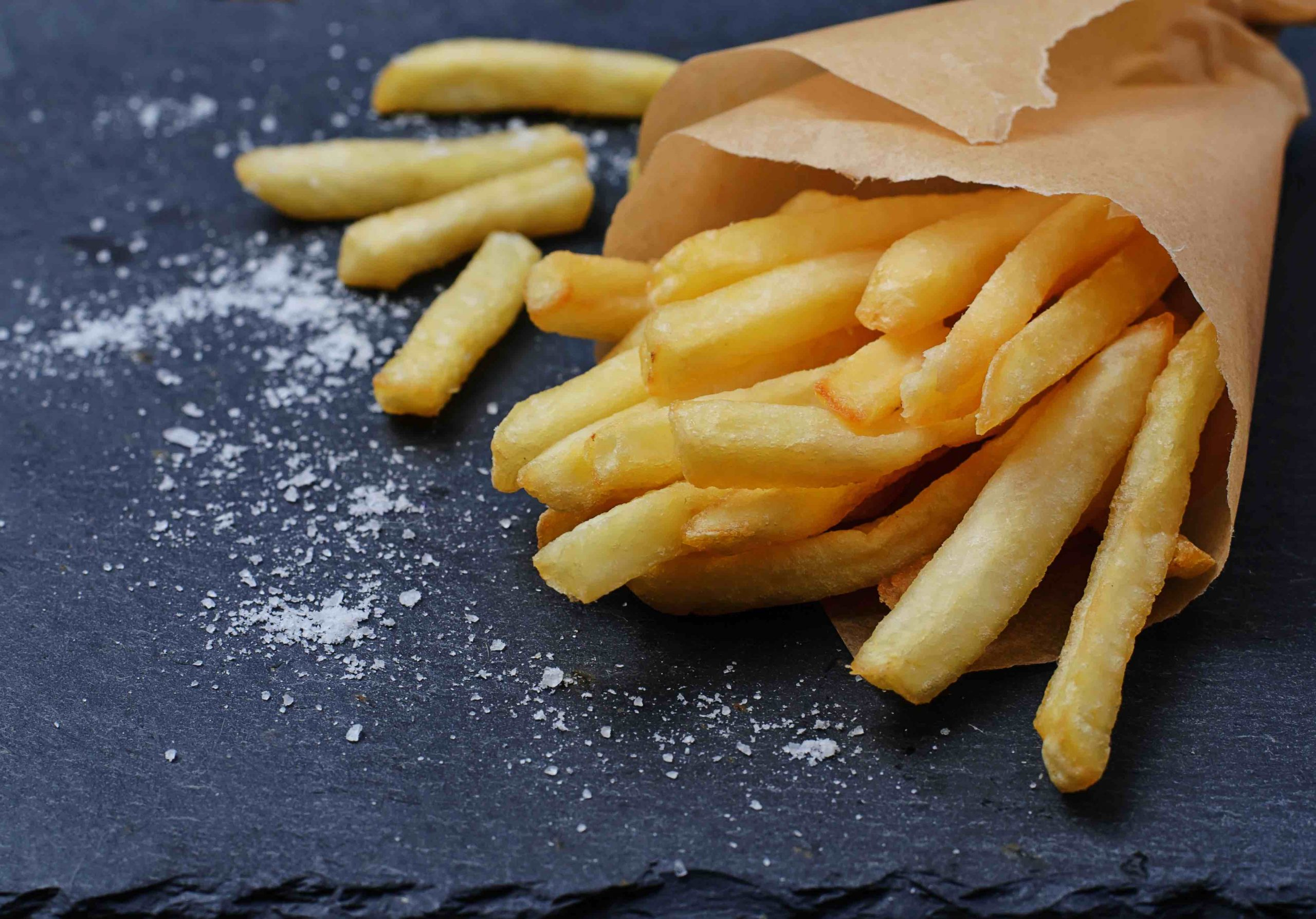 French fries in paper wrapper. Selective focus