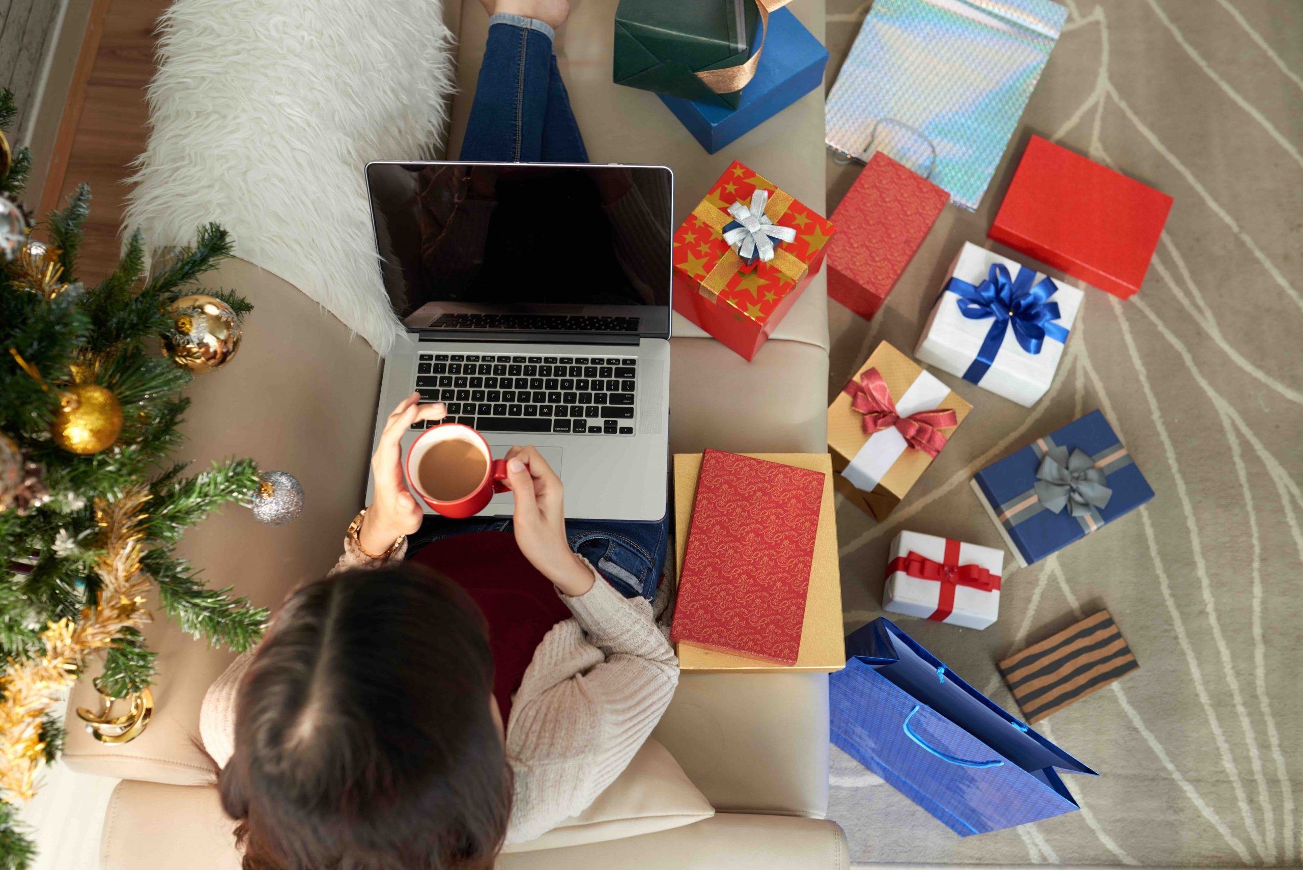 Woman sitting on sofa, drinking coffee and searching for sale on Christmas presents. Gift boxes are scattered around