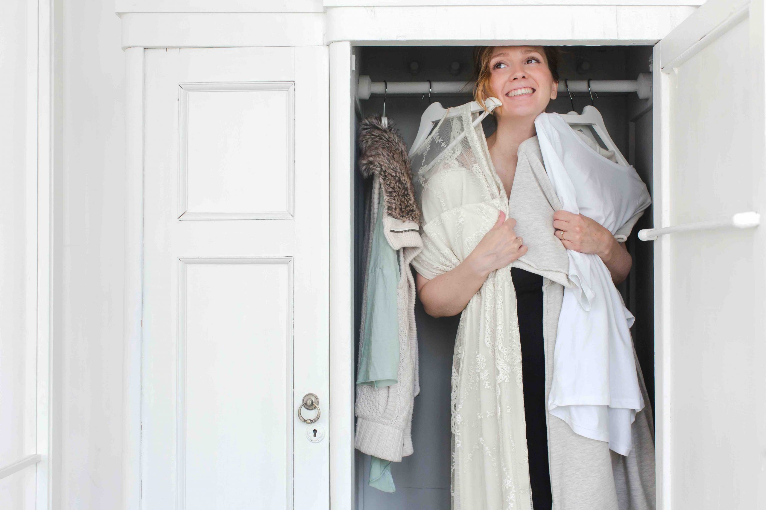 Woman laughs while choosing clothes in the closet