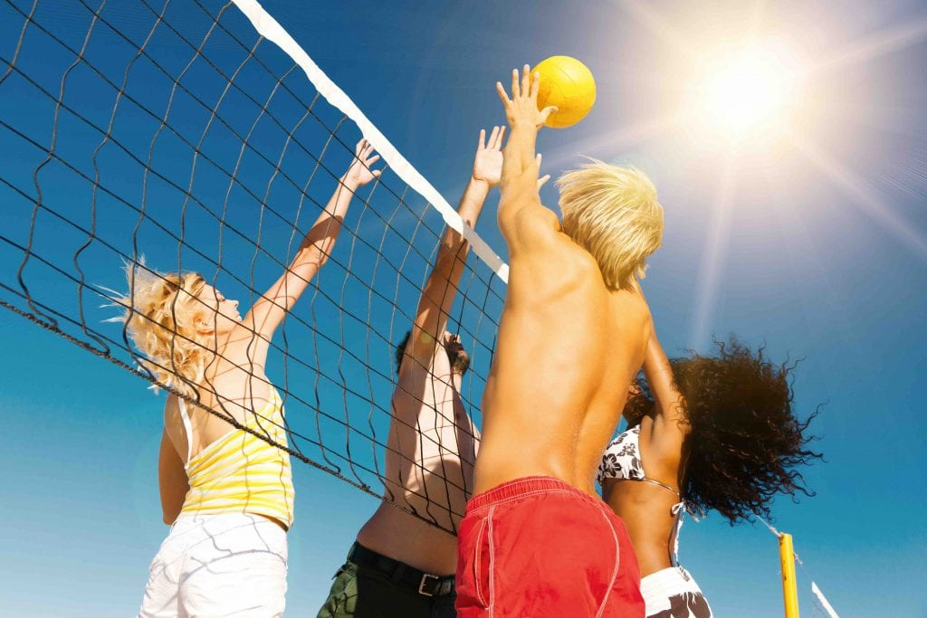 Diverse people playing volleyball outdoors